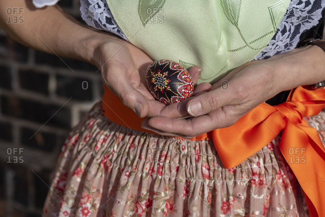 A woman wears the Sorbian costume, holding an ornamented Easter egg in her hands.