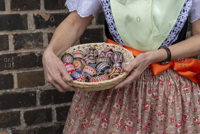 A woman is wearing the Sorbian costume, holding a basket with decorated Easter eggs in her hands.