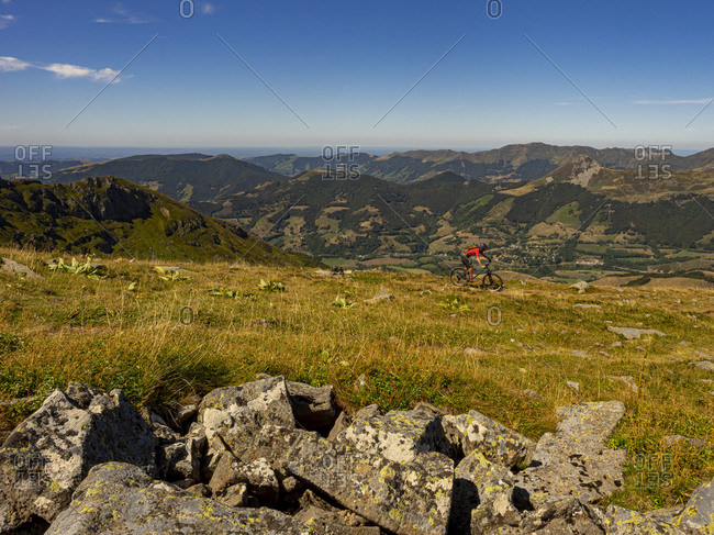 Mountain bikers on the single track GR 400 below the summit of the Plomb du Cantal. View of the Vallee de la Cere valley. Left in the picture: L'Arpon du Diable, right the Puy Griou. Monts du Cantal, Massif Central, Saint-Jacques-des-Blats, Cantal France
