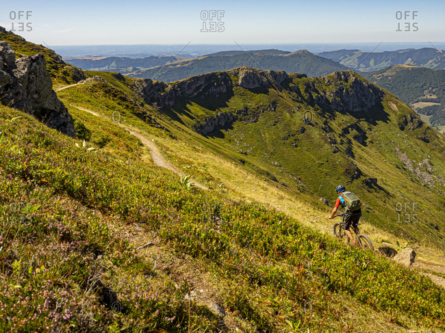 Mountain bikers on the single trail GR 400 below the Plomb du Cantal towards L'Arpon du Diable. View towards the Vallee de la Cere valley. Monts du Cantal, Massif Central, Saint-Jacques-des-Blats, Cantal France