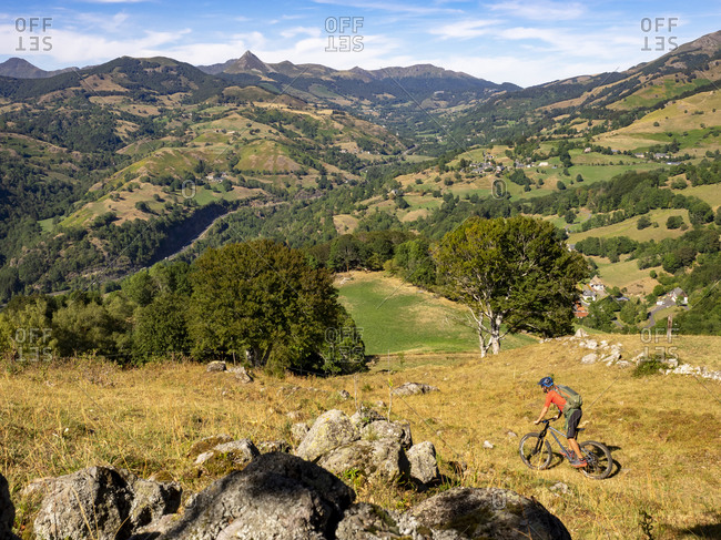Mountain bikers on a single trail, descent over mountain pasture towards Thiezac, in the background Puy Mary. Monts du Cantal, Massif Central, Saint-Jacques-des-Blats, Cantal France