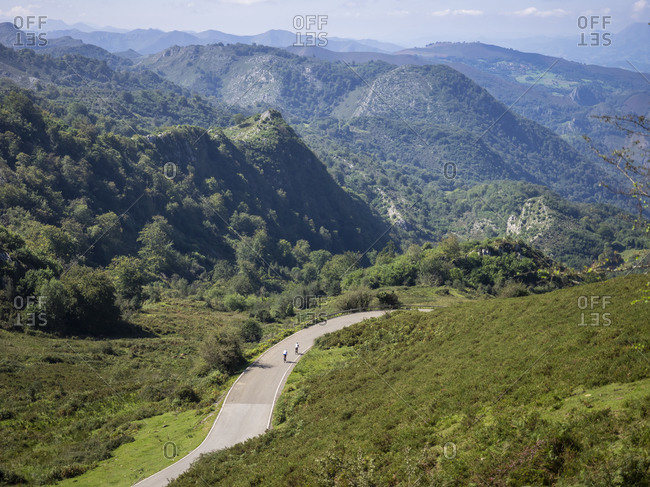 Road cycling in Asturias, northern Spain. Racing cyclist on a steep mountain road near the Lagos de Covadonga. In the Picos de Europa / Parque Nacional de los Picos de Europa. Cantabrian Cordilleras, Principado de Asturias, Spain.