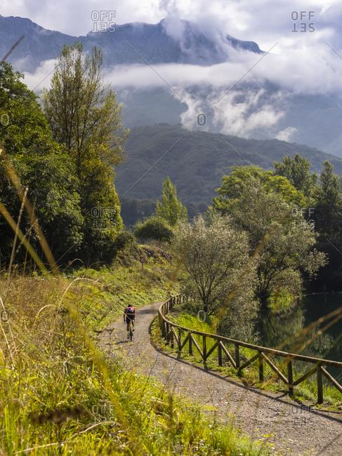 "Road cycling in Asturias, northern Spain. Racing cyclist on the lake ""Embalse de Valdemurrio"" in the mountains near Proaza Principado de Asturias, Spain"