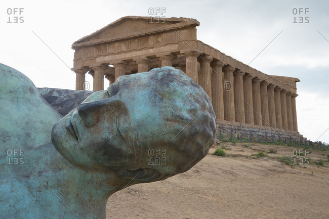 January 15, 2020: Modern sculpture of Icarus in front of the Temple of Concordia, Valley of the Temples, Agrigento, Sicily, Italy
