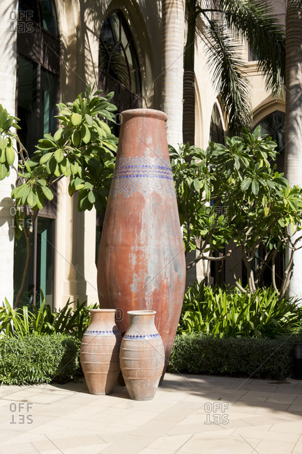 Trio of large decorative weathered earthenware vases standing outdoors in the sunshine in a courtyard or park in front of a grove of palm trees in Dubai, United Arab Emirates