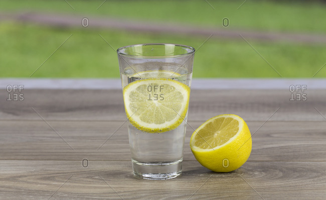 Glass of fresh cold mineral water with a slice of fresh lemon for a tangy taste on a table with yellow roses in a healthy diet and lifestyle concept