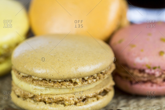 Batch of freshly baked colorful macarons made from egg white, coconut, almond and sugar and filled with ganache or butter cream, tilted angle view