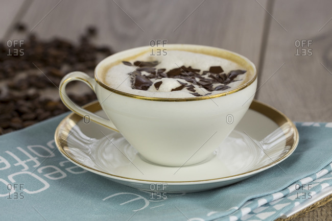 Cup of freshly brewed aromatic cappuccino coffee topped with milky froth and grated chocolate flakes served on a pretty napkin on a rustic wooden table