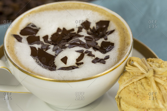 Porcelain cup and saucer of delicious freshly made aromatic cappuccino topped with milky foam and chocolate flakes served with crunchy golden cookies