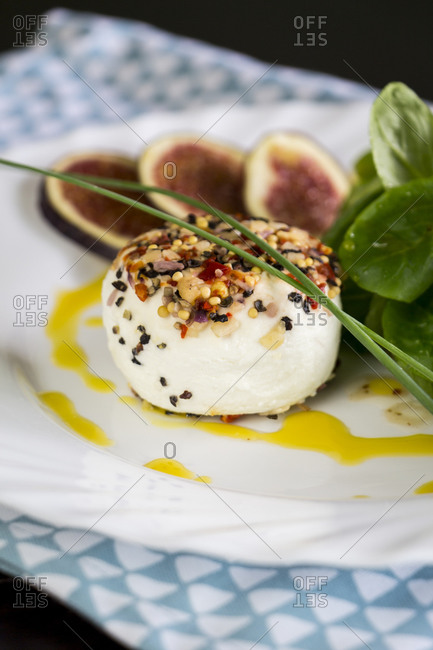 Delicious appetizer of seasoned goats milk cheese with fresh ripe sliced figs and leafy green herb salad served on a plate