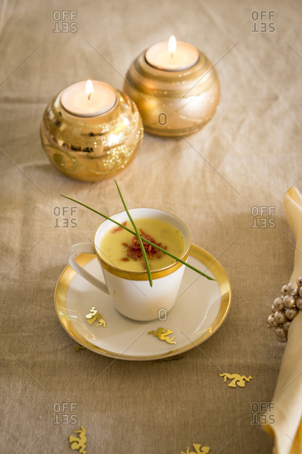Cup of potato and ham soup garnished with serrano peppers served as an appetizer for Christmas dinner with gold trim and golden Xmas candles burning in the background as table decoration