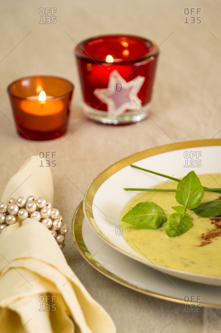 Stylish bowl of ham and potato soup seasoned with pungent serrano peppers and garnished with fresh basil and chives for a hot appetizer to a winter meal