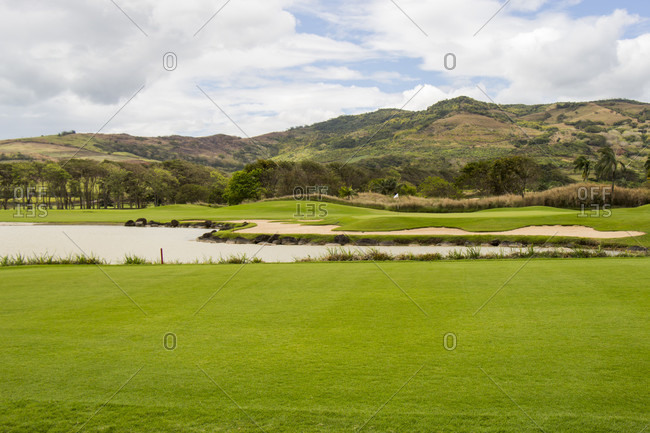 Scenic landscape of lush green fairways on a golf course in Mauritius with a lake and distant mountains