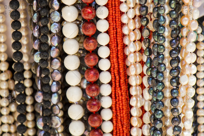 Strings of matched cultured pearl necklaces with black and white lustrous nacre beads hanging on a display in a shop in Mauritius