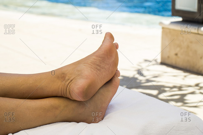 Close up Bare Feet on White Towel at the White Sand Beach. Emphasizing Relaxation.