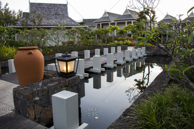 June 15, 2018: Walkway reflected in the calm water of a pond in a landscaped formal garden in a Mauritius resort with stylish accommodation bungalows with open-air verandas set amongst lush tropical vegetation