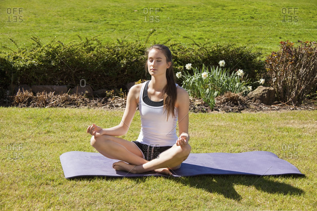 Young woman meditating at the side of a pool sitting cross legged in the lotus position with her eyes closed and serene expression, garden backdrop