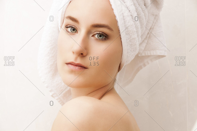 Close up Pretty Young Woman Wrapped in Towels After Bath, Caressing her Face While Looking Down Seriously
