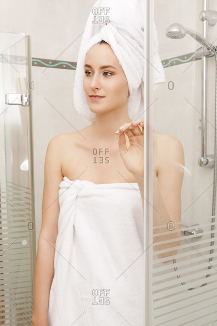 Fresh Young Woman Wrapped with Towels After Bath, Smiling at the Camera While Inside the Shower Cubicle