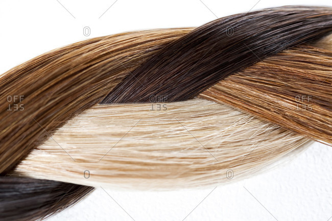 Blond, brown and black hair weaved in a braid over white
