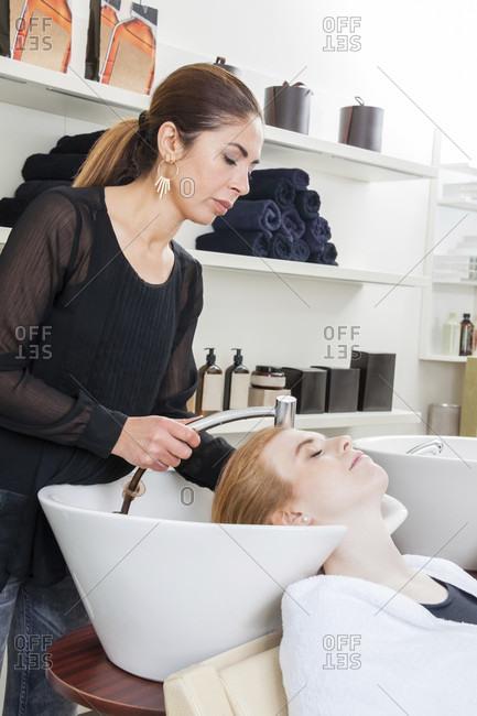 hairstyling professional washing woman hair at the salon