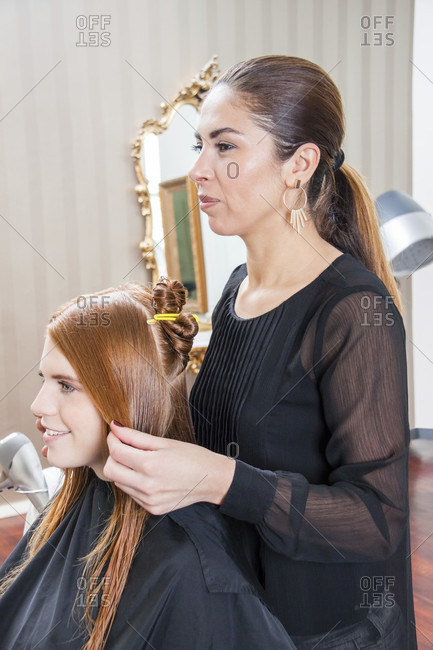 Rear View of Young Woman with Long Red Hair Having Hair Cut by Stylist in Salon