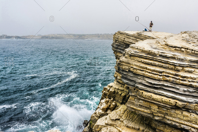 Europe, Portugal, Centro Region, Peniche, lone angler on a ledge by the sea