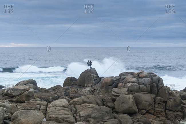 Spain, north coast, Galicia, Costa da Morte, Muxia, place of pilgrimage, couple on rocks