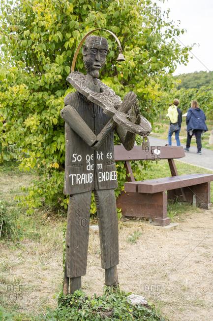 """October 6, 2018: Germany, Rhineland-Palatinate, Schweigen-Rechtenbach, """"Traubendieb"""", wooden figure in the vineyard."""