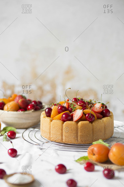 Summer cake with fresh fruit on white table
