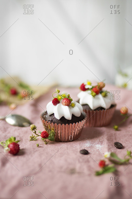 Chocolate cupcake with whipped cream and wild strawberries on the table.