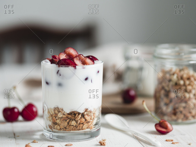 Fermented probiotic kefir or yogurt in glass with granola at the bottom served fresh sweet cherry halves on white wooden rustic table.