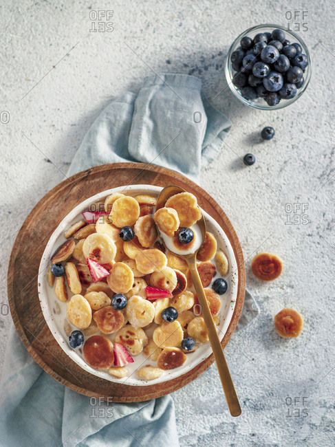 Trendy food - pancake cereal. Milk with cereal pancakes in bowl. Tiny cereal pancakes with berries in craft plate over gray cement background. Copy space