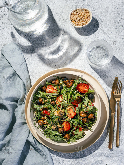Salad with arugula, mini champignons, cherry tomatoes, black olives, pine nuts, nutritional yeast. Top view or flat lay. Copy space. Hard light. Vertical.