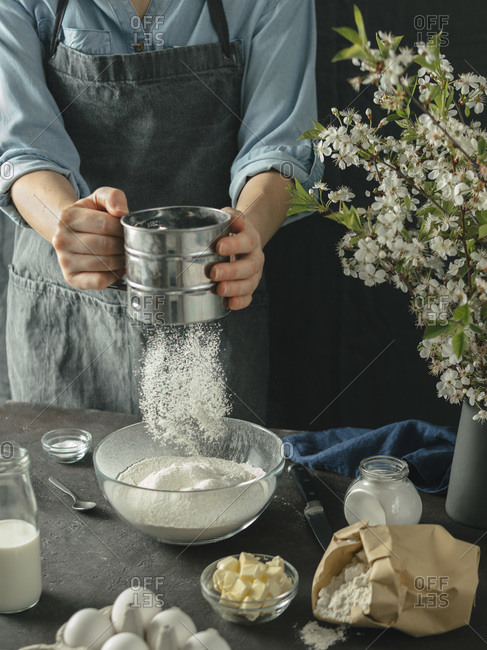 Young woman making cake. Female hands sifting flour from metal sieve in to glass mixing bowl on dark background. Food ingredients and kitchenware with flour, butter, milk and eggs at foreground and bouquet of blossoming cherry or pear branches. Photo series.