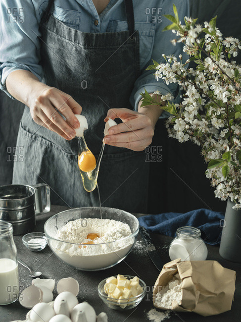 Young woman in blue shirt and gray apron making cake. Female hands break the egg in mixing boul with flour on dark background. Food ingredients and kitchenware with flour, milk, butter and eggs at foreground and bouquet of blossoming cherry or pear branches. Photo series.