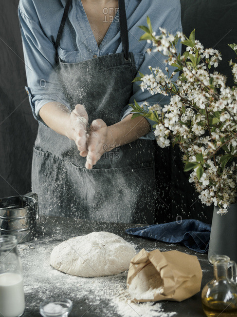 Young woman in blue shirt and gray apron making bread dough. Female hands kneading dough on dark kitchen. Black table with food ingredients - flour, milk, salt, olive oil and bouquet of blossoming cherry or pear branches. Home bread baking. Photo series.