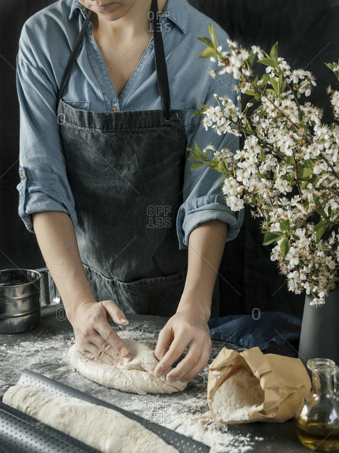Young woman in blue shirt and gray apron making bread dough. Female hands molding of baguette on dark kitchen. Black table with food ingredients - flour, milk, salt, olive oil and bouquet of blossoming cherry or pear branches. Home bread baking. Photo series.