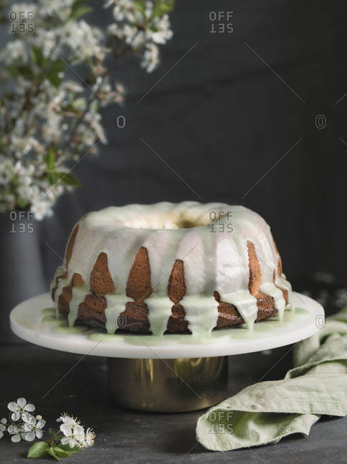 Bundt cake with green matcha glaze on white marble cake stand over dark table with bouquet of blossoming cherry or pear branches. Copy space top over dark wall