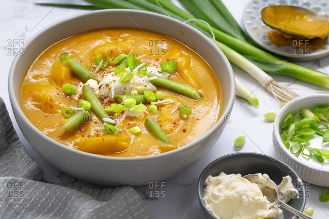 Bowl of pumpkin soup with green beans, sour cream and sliced spring onions.