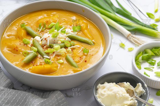 Serving of homemade pumpkin and green bean soup.