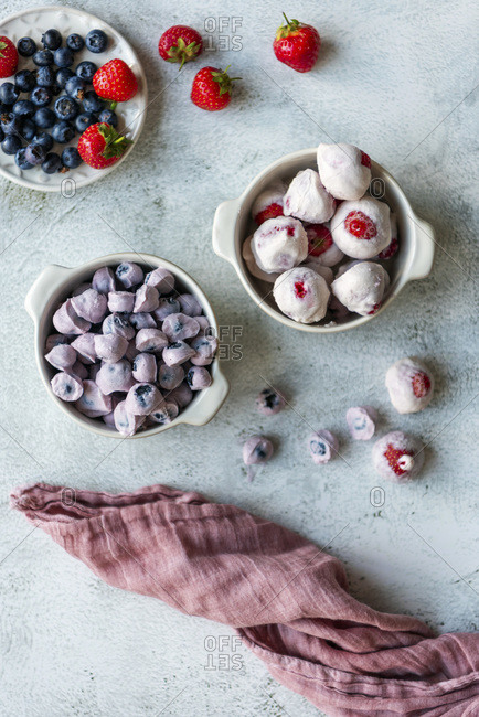 Yogurt bites with blueberries and strawberries in two ceramic bowls photographed on a light background. Fresh blueberries and strawberries accompany.
