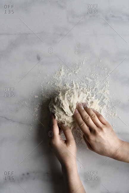 Hands shaping bread dough on a marble counter.
