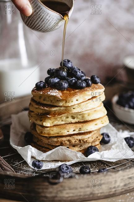 Drizzling honey on pancakes studio shot
