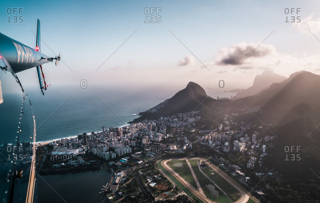 RIO DE JANEIRO, BRAZIL - 22 OCTOBER 2018: Aerial View From Helicopter Of Afternoon Light Rays Shining Through Mountains And Onto South Zone Of Rio De Janeiro City, Brazil