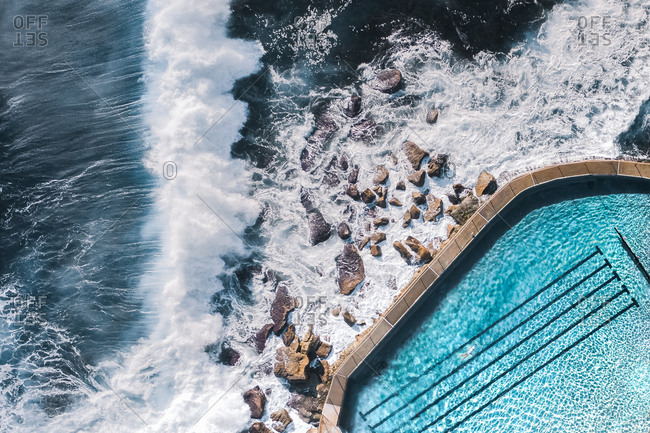 Aerial View Of Large Ocean Waves Breaking Towards Natural Water Coastal Swimming Pool With Person Swimming In Bronte, Sydney, Australia