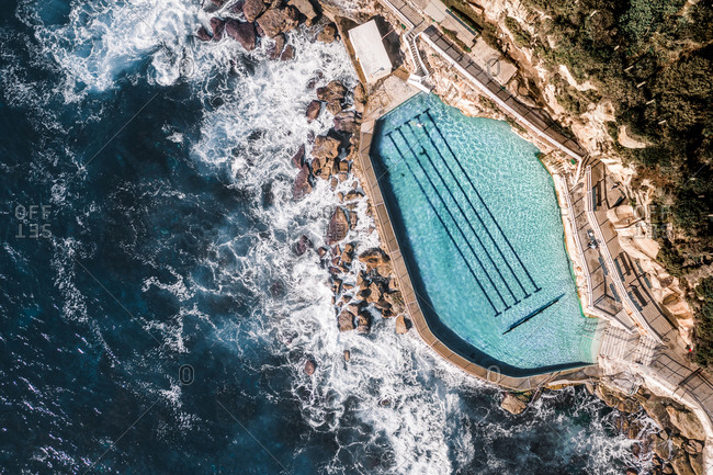 Aerial Top Down View Of Ocean Water Coastal Swimming Pool With Person Swimming In Bronte, Sydney, Australia