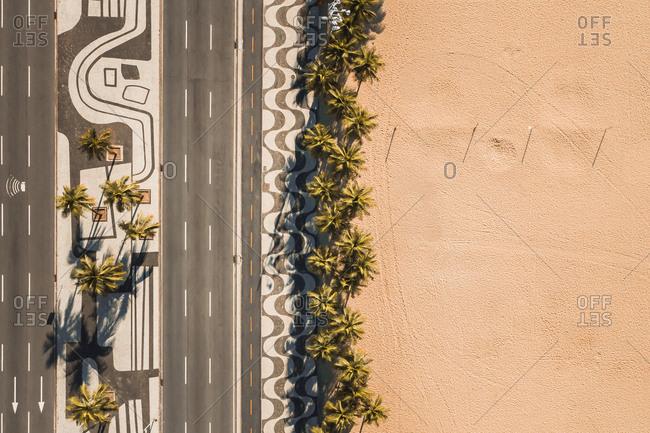 Aerial Top Down View Of Palm Trees On Empty Copacabana Beach, Alongside Famous Mosaic Sidewalk And Avenida Atlantica Road, During Coronavirus Lockdown In Rio De Janeiro, Brazil