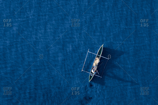 Aerial view of a fisherman and his mirror shadow fishing using a pirogue boat on deep blue ocean waters during sunrise in Dili, Timor-Leste