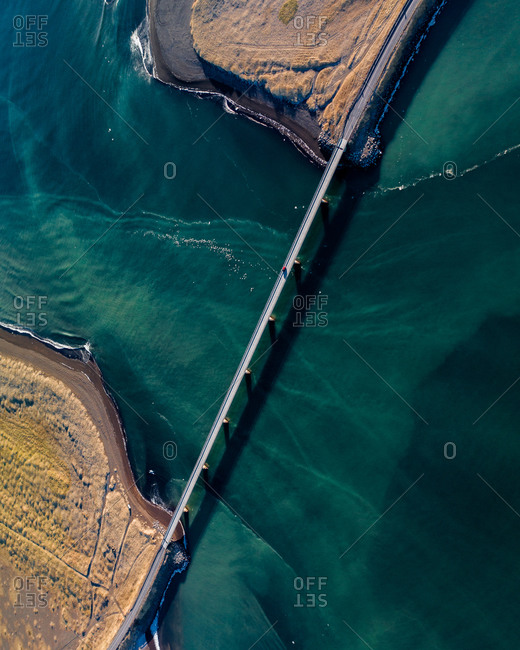 Aerial view of a red car driving through bridge on glacial river Olfusá coming down from the mountains to meet the ocean, Reykjanes Peninsula, Iceland.